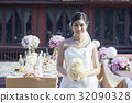 A portrait of beautiful bride holding bouquet and standing in front of romantic setting 32090328