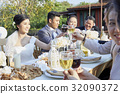 the bride is clinking wine while the others are chatting and toasting together 32090372