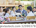 The married couple are raising wine glass while the others are chatting and clinking 32090378