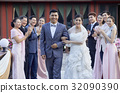 guests are clapping in background of a happy newlywed couple 32090390