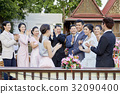 guests are clapping for happy newlyweds outdoors 32090400