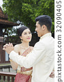 bride and groom are dancing outdoors at wedding reception 32090405