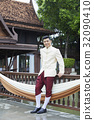 handsome groom is standing, leaning against a balcony and smilling 32090410