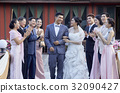 newlyweds are walking with arm in arm and guests are clapping 32090427
