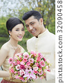 A portrait of a couple holding flowers and smiling. 32090458