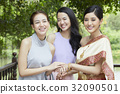 A photo of two girls and a bride holding hands and smiling together  32090501
