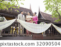 A bride is smiling at her parents in a balcony on her wedding day 32090504