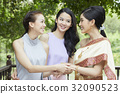 a photo of a bride and two girls taking hands and smiling together 32090523