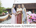 A bride and two bridesmaids are standing and posing outside. 32090543