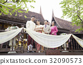 A newlywed and parents are standing on the balcony. 32090573