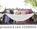 a picture of a happy family standing and smiling on a balcony. 32090605