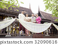 A married couple and parents are standing outside and smiling. 32090616