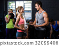 Woman talking with trainer in gym 32099406