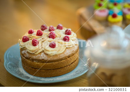 Sponge cake with whipped cream and cherry topping on plate 32100031