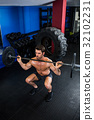 Shirtless man exercising with barbell in gym 32102231
