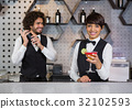 Two bartenders preparing cocktail and serving in bar counter 32102593