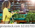 Smiling male staff assisting a woman with grocery shopping 32103703
