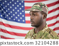 Soldier standing against american flag 32104288