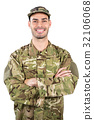 Portrait of smiling soldier standing with arms crossed 32106068