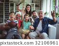 Happy multi-generation family watching soccer match on television in living room 32106961