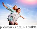 Young guy piggybacking cheerful girlfriend like  32126094