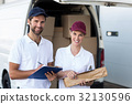 Portrait of delivery man and woman standing with clipboard and parcel 32130596