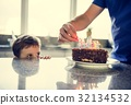 Father and son prepare and decorate choclate birthday cake 32134532