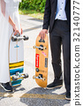 Bride and groom standing and holding skateboard 32140777