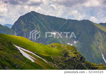 rocky edge on grassy hillside with snow 32144320