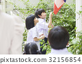 A schoolboy and a schoolgirl are pulling national flag at an assembly 32156854