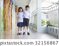 a photo of a schoolboy and a schoolgirl standing, putting arms on shoulders, smiling 32156867