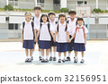A photo of students standing and smiling happily in the school yard 32156951