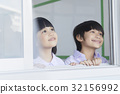 Two schoolchildren are smiling and looking out from the window. 32156992