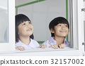 Children are smiling and looking at something outside the class. 32157002