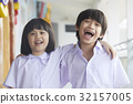 Children are laughing and putting arms on each other's shoulder. 32157005
