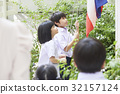 a picture of a couple of pupils standing in the schoolyard and slowly raising the flag 32157124