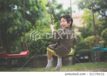 Asian child in kimono playing on swing i 32176010