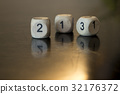 Rolling three dice on a wooden desk. 32176372