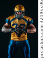 American football player holds ball in hands 32195596