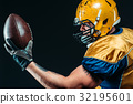 American football player with laced ball in hands 32195601