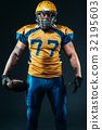 American football player holds ball in hands 32195603