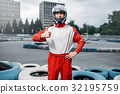 Kart driver in helmet, karting track on background 32195759