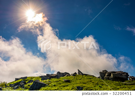 sunburst on a blue sky with clouds over mountains 32200451