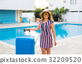 Happy young woman with blue luggage arriving to 32209520
