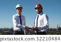 Two young male architects or engineers make deal 32210484