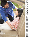 father help daughter to fasten a seat belt 32219914