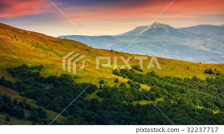 mountain ridge with peak behind hillside at sunset 32237717