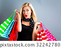 Happy young woman holding shopping bags  32242780