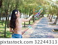Girl in swimsuit making soap bubbles on summer vacation 32244313