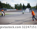 Man holding and waving the checkered flag at the 32247151